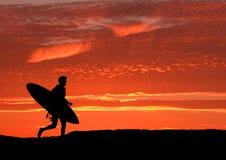Persona que practica surf que corre hacia fuera al mar Fotografía de archivo libre de regalías