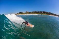 Persona que practica surf que da vuelta a la onda azul Fotos de archivo libres de regalías
