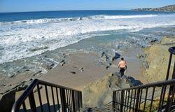 Persona que practica surf que dirige hacia fuera a la resaca en la playa en Laguna Beach, California de la calle de los arroyos Fotografía de archivo
