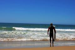Persona que practica surf que mira el océano Foto de archivo