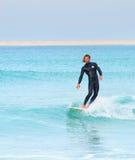 Persona que practica surf que monta un vawe Fotos de archivo