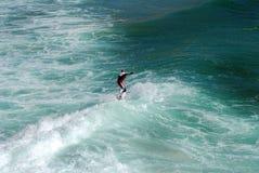 Persona que practica surf que monta una onda Fotos de archivo