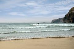 Persona que practica surf que practica surf cerca de los acantilados del ballybunion Fotografía de archivo libre de regalías