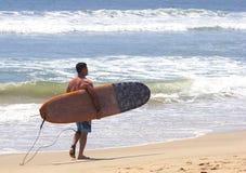 Persona que practica surf que recorre con la tabla hawaiana Fotografía de archivo