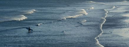 Persona que practica surf que recorre en el mar Imagen de archivo