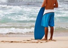 Persona que practica surf que se coloca en la playa Imagen de archivo libre de regalías