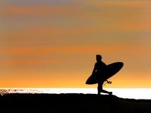 Persona que practica surf que se ejecuta hacia fuera al mar Fotos de archivo
