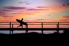 Persona que practica surf que se ejecuta a la playa Foto de archivo libre de regalías