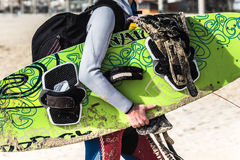 Persona que practica surf que sostiene una tabla hawaiana y que camina en la playa Imagen de archivo libre de regalías