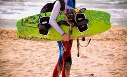 Persona que practica surf que sostiene una tabla hawaiana y que camina en la playa Fotografía de archivo libre de regalías