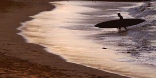 Persona que practica surf retroiluminada en la puesta del sol Fotografía de archivo libre de regalías