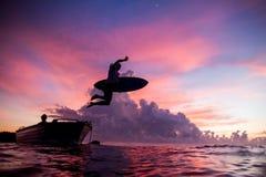 Persona que practica surf rosada del cielo en la salida del sol Fotos de archivo