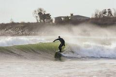 Persona que practica surf y espray en día ventoso Fotografía de archivo
