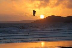 Persona que practica surf y puesta del sol de la cometa Imagen de archivo