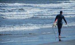 Persona que practica surf y su tablero Imagen de archivo libre de regalías