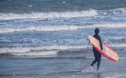 Persona que practica surf y su tablero Foto de archivo