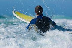 Persona que practica surf y tarjeta en el mar con las ondas Imagen de archivo