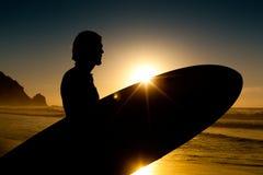 Persona que practica surf y tarjeta en sol de la tarde Foto de archivo libre de regalías