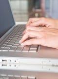 Persona que pulsa en una computadora portátil moderna Imagen de archivo libre de regalías