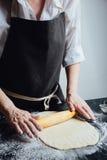 Persona que rueda la pasta hecha en casa de la galleta Fotos de archivo libres de regalías