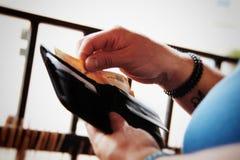 Persona que saca el dinero de su cartera imagenes de archivo