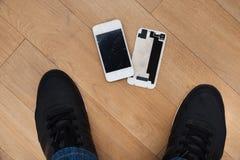 Persona que se coloca cerca del teléfono móvil quebrado Fotos de archivo libres de regalías