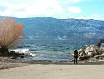 Persona que se coloca en orilla del lago en invierno Imagenes de archivo