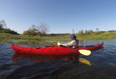 Persona que se sienta en una canoa en el estuario que mira hacia dos Eagles calvo Imagenes de archivo