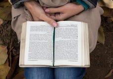 Persona que sienta en la lectura de tierra un libro (biblia) Fotografía de archivo libre de regalías
