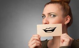 Persona que sostiene delante de su boca una tarjeta foto de archivo