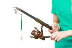 Persona que sostiene la caña de pescar, equipo de giro Fotografía de archivo libre de regalías