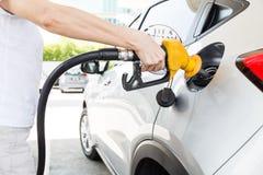 Persona que sostiene la gasolina de relleno de la boca amarilla en el coche foto de archivo