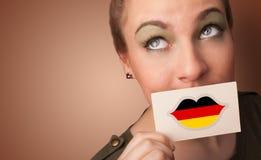 Persona que sostiene la tarjeta de la bandera de Alemania imágenes de archivo libres de regalías