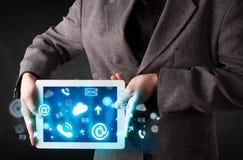 Persona que sostiene una tableta con los iconos azules de la tecnología Imágenes de archivo libres de regalías