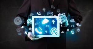 Persona que sostiene una tableta con los iconos y los símbolos azules de la tecnología Imagenes de archivo