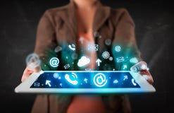 Persona que sostiene una tableta con los iconos y los símbolos azules de la tecnología Fotos de archivo