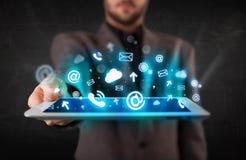 Persona que sostiene una tableta con los iconos y los símbolos azules de la tecnología Foto de archivo libre de regalías