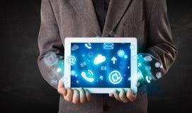 Persona que sostiene una tableta con los iconos y los símbolos azules de la tecnología Fotografía de archivo libre de regalías