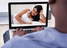 Persona que tiene charla video con la mujer Foto de archivo