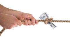 Persona que tira del billete de banco atado en una cuerda Imágenes de archivo libres de regalías