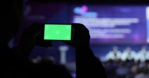 Persona que toma el vídeo y las fotos en smartphone móvil en la conferencia Pantalla verde con el mate del luma incluido Negocios