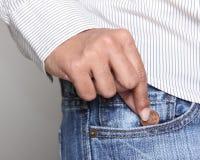Persona que toma un penique del bolsillo de la mezclilla Fotografía de archivo