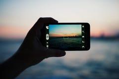 Persona que toma una foto de la puesta del sol asombrosa usando cámara elegante del teléfono Imagenes de archivo