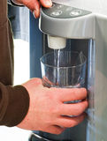Persona que usa el dispensador del agua Fotografía de archivo
