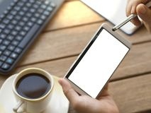 Persona que usa el teléfono elegante con la pluma y con la pantalla blanca en blanco del teléfono fotografía de archivo