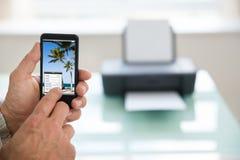 Persona que usa el teléfono móvil para imprimir la foto imagen de archivo libre de regalías
