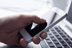 Persona que usa el teléfono mientras que trabaja en un ordenador portátil Foto de archivo libre de regalías