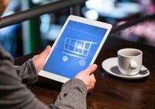 Persona que usa la tableta con el icono y el café de la carretilla de las compras fotografía de archivo