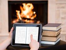 Persona que usa la tableta digital cerca de la chimenea Fotos de archivo
