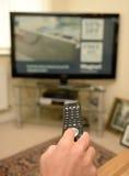 Persona que usa la TV teledirigida Fotos de archivo